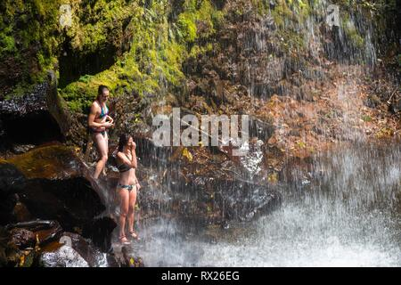 Two Young Women in Bikinis standing under Waterfall in Tropical Cloudforest at end of famous Lost Waterfalls Trail near Boquete in Panama Highlands - Stock Image