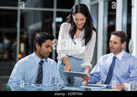 Businesswoman discussing with colleagues over digital tablet - Stock Image