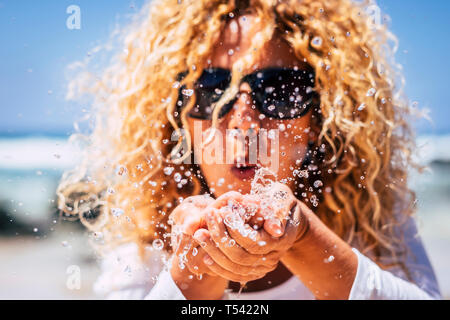 Summer fresh holiday vacation concept with blonde curly beautiful young woman blowing water from hands - fun and play caucasian people under the sun - - Stock Image