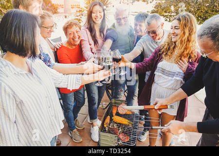 Happy family cheering and toasting with red wine glass at barbecue party - People with different ages having fun drinking and grilling meat - Stock Image
