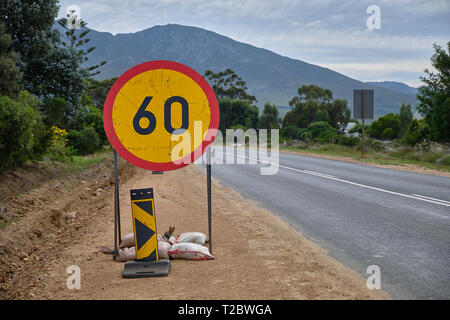 Road sign to reduce speed to 60 km/h on side of road with mountains in background - Stock Image