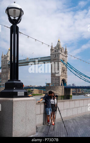 London, England. 4th July 2018. A couple take a selfie with a tripod near London's Tower Bridge on another very hot day. The present heatwave is set to continue. ©Tim Ring/Alamy Live News - Stock Image