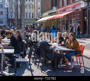People enjoying refreshments at outdoor restaurant tables on a sunny spring morning, Exhibition Road, South Kensington, London, England, UK - Stock Image