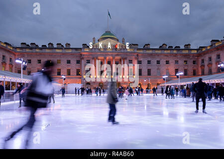 Skaters at dusk on the pop-up ice rink at Somerset House, London, England - Stock Image