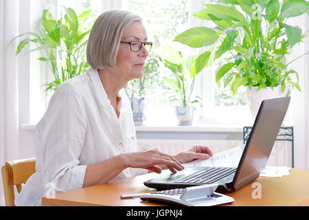 Relaxed senior woman at home with a calculator and lots of receipts in front of her laptop making her annual tax - Stock Image