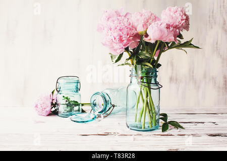 Beautiful pink Peony flowers in an antique blue mason jar over a white rustic wood table background  with copy space for your text. - Stock Image