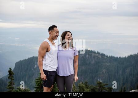 Happy couple hiking on mountaintop - Stock Image