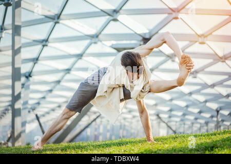Close up of attractive athletic man practicing yoga and warming up in modern park at green grass outdoors. - Stock Image
