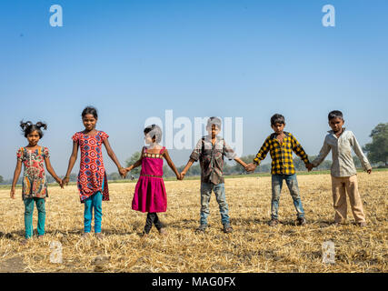 Children of agriculture laborer playing in field. - Stock Image