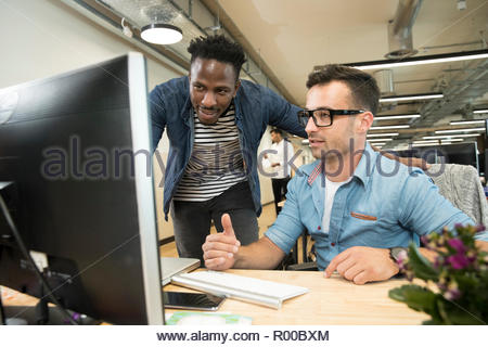 Colleagues using computer - Stock Image