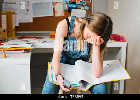 Tired, stressed female college student studying - Stock Image