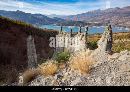 France, Hautes-Alpes, geological site of the Demoiselles Coiff?es of Sauze-du-Lac, in the background the lake of Serre-Pon?on - Stock Image