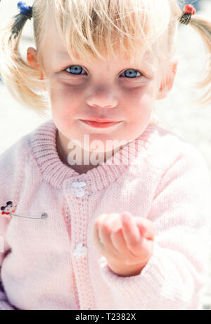 Beautiful Young Blonde 3 Year Old Girl Looks at the Camera, USA - Stock Image