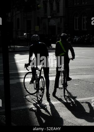 Two cyclists waiting at traffic lights - Stock Image