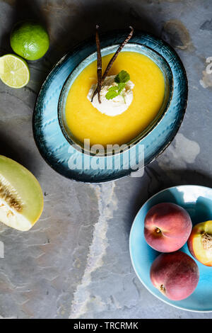 Refreshing summer fruit soup with Galia melon and peaches, topped with a scoop of vanilla ice cream - Stock Image