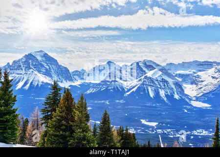 Bright afternoon sun breaking out of low cumulus clouds over Mount Victoria glacier and the Canadian Rockies at Lake Louise near Banff National Park. - Stock Image