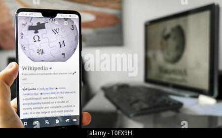 Wikipedia app smartphone computer desk background - Stock Image