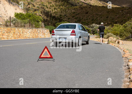 Man walking by the a broken down car - Stock Image