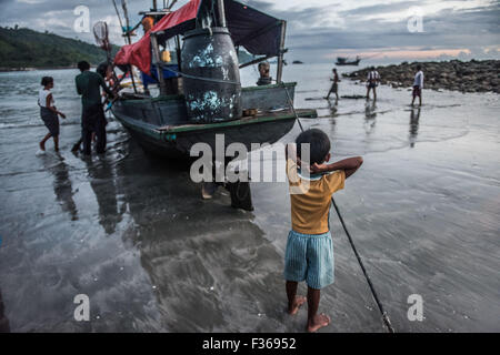 Child by fishing boat, San Hlan beach, Myanmar. - Stock Image