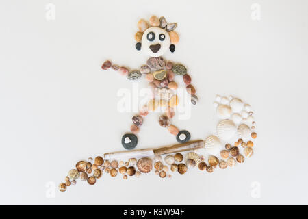 natural art, craft, picture of person surfing, made from pebbles, shells, - Stock Image