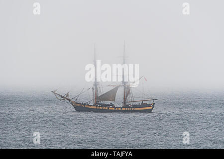 Mousehole, Cornwall, UK. 26th May 2019. UK Weather.  Cornish 'mizzle'  greeted this tall ship heading towards Penzance today on an overcast bank holiday sunday. Credit Simon Maycock / Alamy Live News. - Stock Image