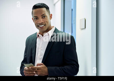 Businessman holding smart phone while standing in hotel lobby - Stock Image