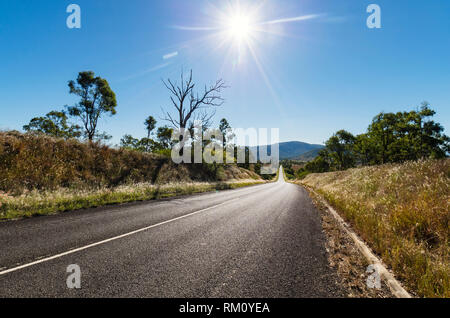 A view down an empty road outside Brisbane with a midday sun. - Stock Image