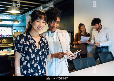 Smiling businesswomen using digital tablet in office - Stock Image