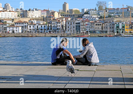 A young couple sitting together eating on the quay by the Douro River on a spring afternoon in the city of Porto, Portugal Europe   KATHY DEWITT - Stock Image