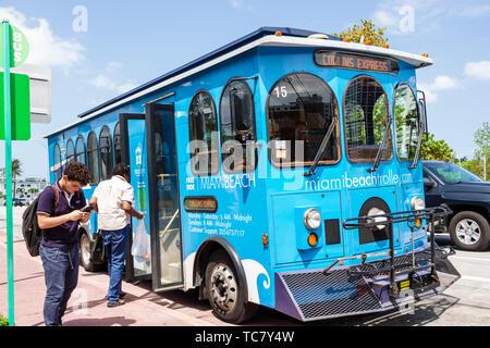 Miami Beach Florida Normandy Isle Collins Express free trolley bus public transportation Hispanic man passenger riders boarding - Stock Image