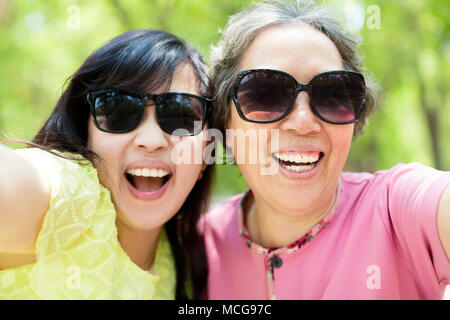 happy senior mother and daughter taking selfie - Stock Image