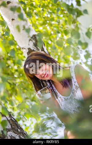 Attractive teenager girl is drinking coffee in nature looking at camera smiling happy - Stock Image