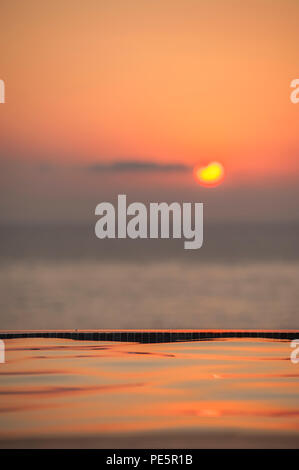 A setting sun over an infinity pool and the Mediterranean sea - Stock Image