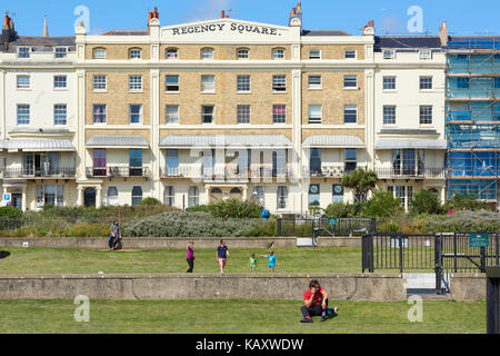 Public enjoying the sun in Regency square in Brighton, East Sussex, UK. - Stock Image
