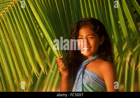 Polynesian girl in front of green palm fronds on Cook Islands in sunset light - Stock Image