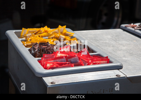 Sauce sachets of tomato, brown and mustard sauce,in fast-food outlet on metal unit.Convenient,basic,colourful,not - Stock Image