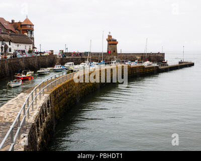 Curved sea wall at Lynmouth, Devon, UK, protects the fishing and pleasure craft in the small harbour - Stock Image