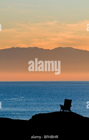 An adirondack-style chair is silhouetted against the ocean and the Olympic Mountains at sunset near Victoria BC. - Stock Image