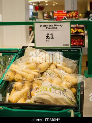 Morrisons supermarket have put 1kg bags of slightly misshapen or outside specification parsnips on sale in 1 kg - Stock Image