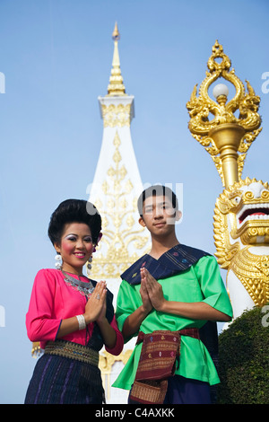 Thailand, Nakhon Phanom, That Phanom.  Dancers in ceremonial Isan dress with the chedi at Wat Phra That Phanom in - Stock Image