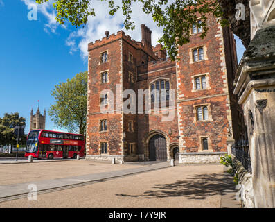 Lambeth Palace London. Morton's Tower with Parliament and red London Bus. Red brick Tudor gatehouse forming the entrance to Lambeth Palace London UK - Stock Image