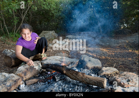 girl roasting a marshmallow in the campfire - Stock Image
