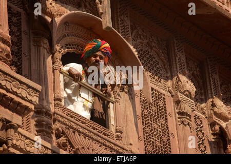 Rajasthani man looking out from window in carved facade at Mehrangarh Fort, Jodhpur, Rajasthan, India - Stock Image