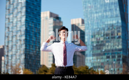 Businessman taking a rest outdoors during daytime - Stock Image