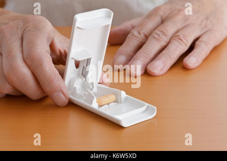 Two hands on a wooden tabletop holding a white plastic pill or tablet cutter with one big orange tablet pill inside, copy space - Stock Image