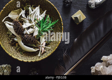 Bowl of Mixed Herbs with Crow Feather and Stones on Black Wood - Stock Image