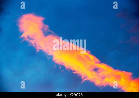 A long cloud lit up at sunset over Ambleside, Cumbria, UK. - Stock Image
