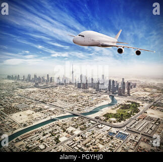 Huge commercial jetliner flying above Dubai city, UAE. Modern and fastest mode of transportation, symbol of luxury and business traveling. - Stock Image