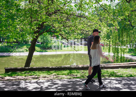 Park sunny young people, view of two young people walking through the Park im Karola Marcinkowskiego on a summer morning, Poznan, Poland. - Stock Image