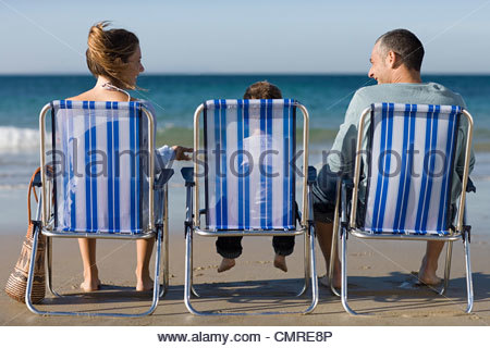 Family in deckchairs by the sea - Stock Image